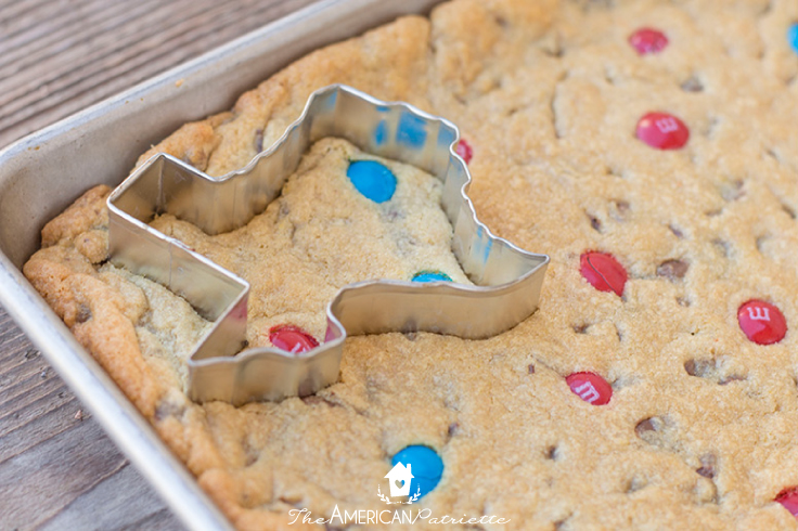 using a cookie cutter to cut the Texas shape out of the chocolate chip cookie dough